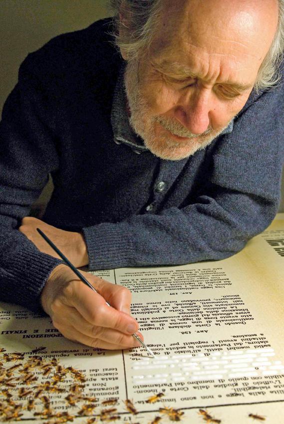 Ritratto di Emilio Isgrò al lavoro nel suo studio mentre cancella la Costituzione Italiana