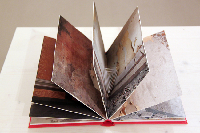 Silvia Camporesi      Apice, 2013    installation view      Giclée print and kirigami intervention    8 photograpies cm 24x36, rebinding      Courtesy: the artist and the gallery