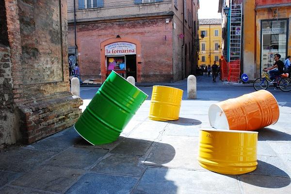 Andrea Mazzola, Economy of pinball, 2014, installazione,12 barili di petrolio in lamiera verniciata (Piazza Grimoldi)