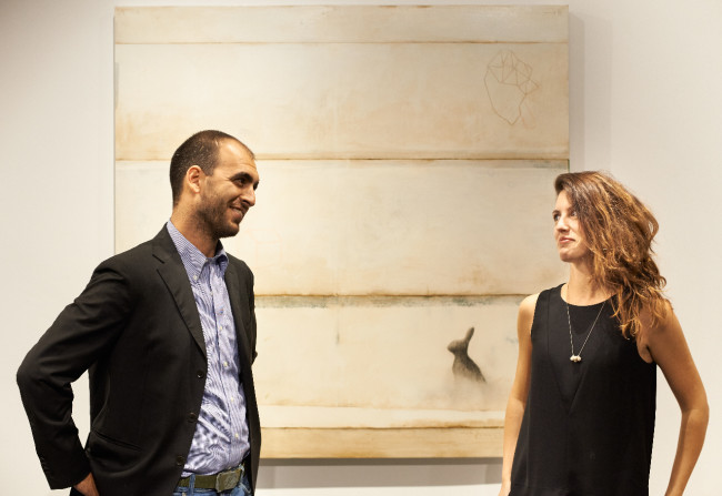 Martina e Stefano Gagliardi nella nuova sede de Il Vicolo a Milano, alle loro spalle un'opera di Mirko Baricchi