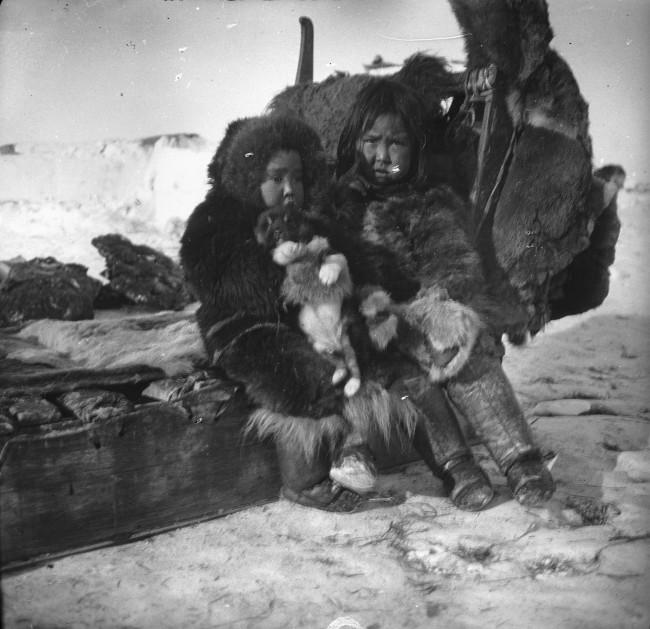 Due bambini sulla slitta il giorno della partenza della spedizione del bicentenario (Jubilæumsekspeditionen, 1920-1923) dopo la sosta a Igdloluorssuit, vicino a Thule Igdloluorssuit, 1921 Fotografo Lauge Koch © Arktisk Institut