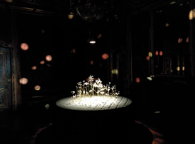 """""""BLOW"""" di KENSUKE KOIKE Decine di piccoli fiori metallici in ottone, danzano nella sala. Ispirato dalla natura dei profumi, alla loro volatilità percepibile soltanto attraverso l'olfatto, l'artista lo trasforma in un effetto puramente visivo ed emozionale"""