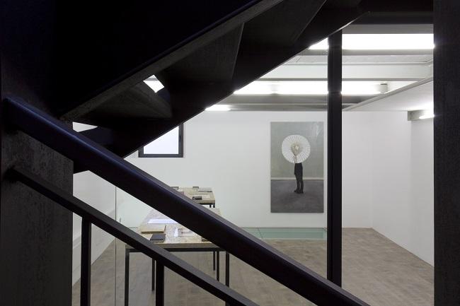 su parete di fondo, Linda Carrara, Behind, olio e acrilico su tela, 200x110, 2013. Sui tavoli installazione taccuini e dipinti, 2012-2014