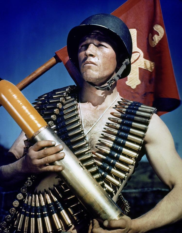 Un soldato statunitense in posa con le cartucciere e il vessillo dell'Artiglieria. © National Archives And Records Administration