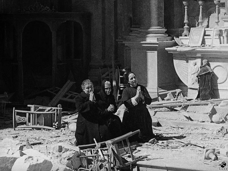 Donne pregano tra le rovine della chiesa di S. Anna, Cagliari, febbraio 1943. © Istituto Luce – Cinecittà