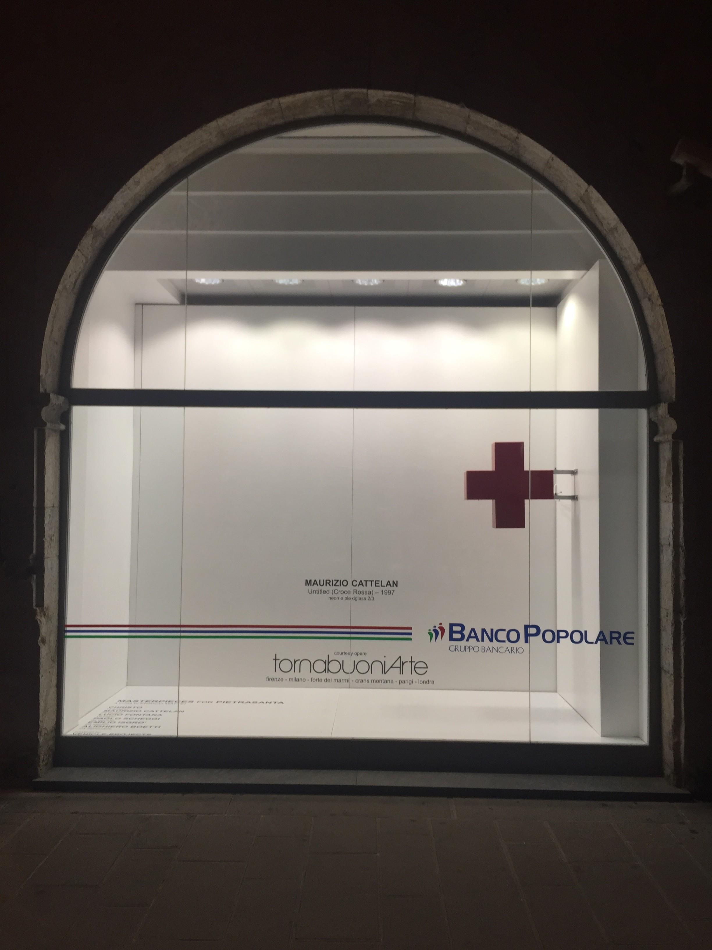 MAURIZIO CATTELAN, Untitled (Croce Rossa),, 1997, neon e plexiglass 2/3, cm. 60x75x20. Veduta dell'allestimento, vetrina banco Popolare di Pietrasanta. Courtesy TornabuoniArte