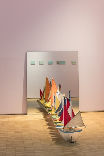 Terra inquieta, veduta della mostra (Francis Alÿs, Untitled (Studio per / Study for Don't Cross the Bridge Before You Get to the River), 2006-2009, installation composed of thirty shoe-boats and one mirror: glass, leather, wood, foam, thread, plastic, corrugated plastic, fabric and steel, 120x100x325.4 cm Courtesy Francis Alÿs and David Zwirner, New York/London), La Triennale, Milano © Foto Gianluca Di Ioia