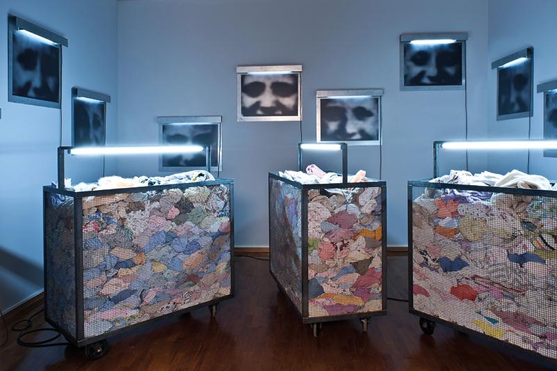 Christian Boltanski, Containers, 2010, carrelli, abiti, neon, dimensioni ambientali. Courtesy: Galleria d'Arte Moderna, Torino
