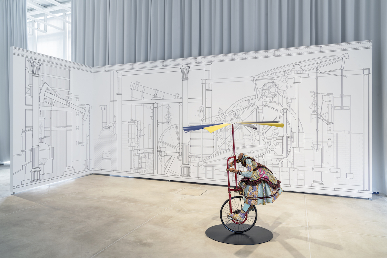 Veduta della mostra IMPREVEDIBILE, Centro Arti e Scienze Golinelli, Bologna. A parete: Pablo Bronstein, The Age of Steel, 2014-2015; Al centro: Yinka Shonibare MBE, Girl on Flying Machine, 2008. Foto: OKNOstudio