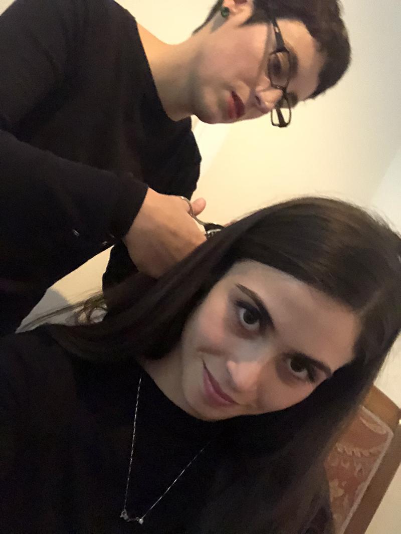 Elyse Galiano durante il vernissage taglia una ciocca di capelli ad una delle visitatrici con la quale realizzerà una piccola opera dedicata che consegnerà al finissage il 13/01/2018