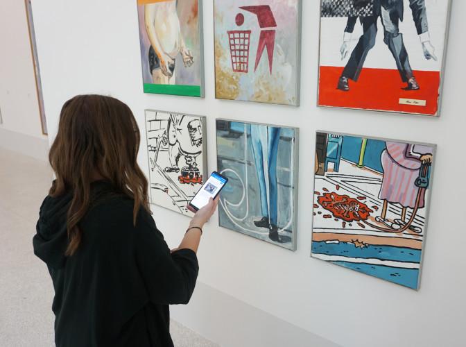 Una visitatrice davanti a un'opera di Martin Kippenberger attiva il Chatbot. Foto Museion © Estate of Martin Kippenberger, Galerie Gisela Capitain, Cologne
